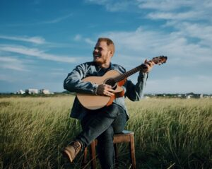 happy young man playing guitar in rural meadow on sunny day