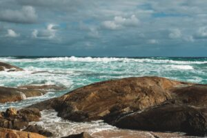 picturesque azure sea waves rolling on rough stony coast