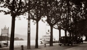 an old photo of cars parked on the street near a docking area