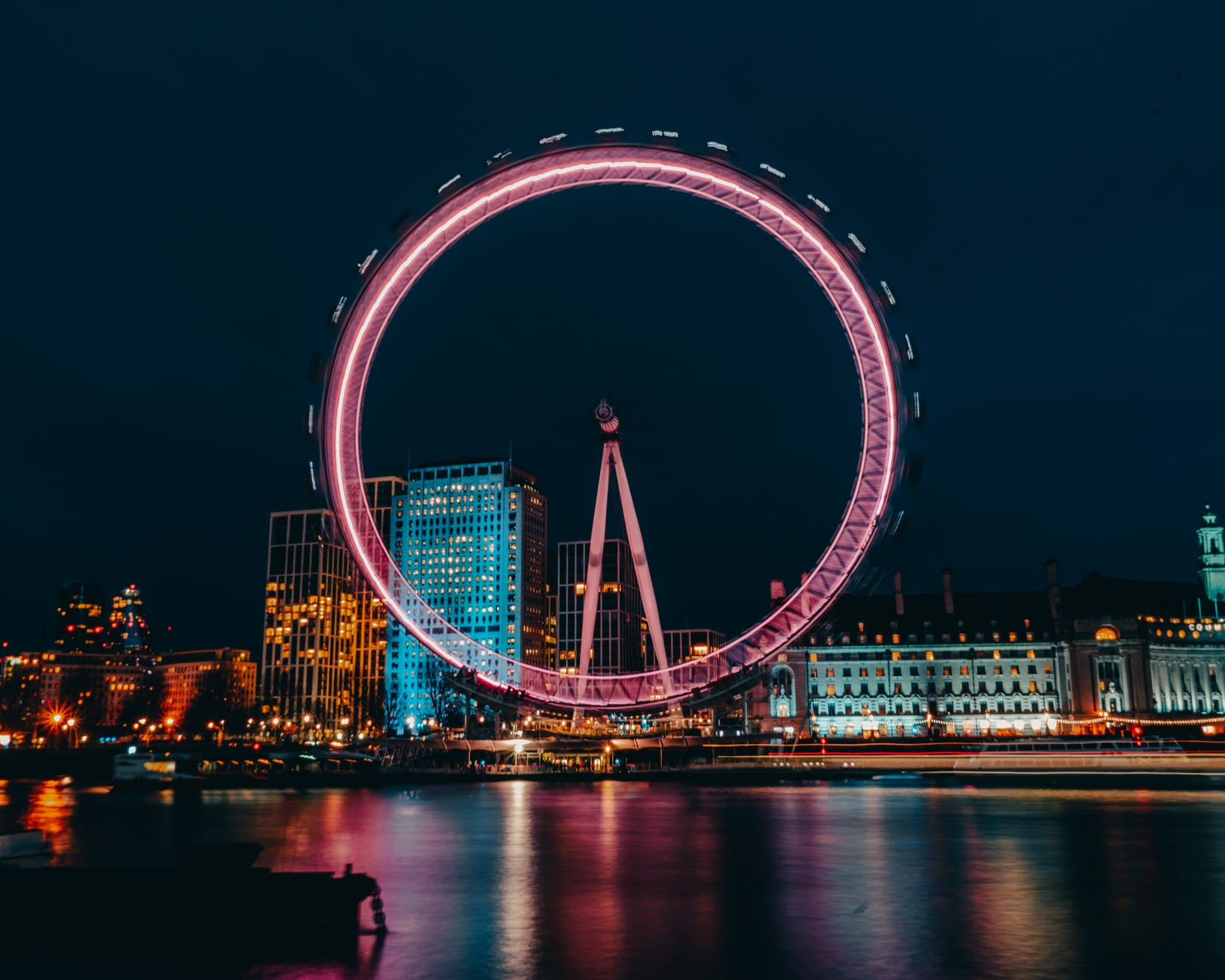 photo of luminous ferris wheel in modern city district on river bank at night